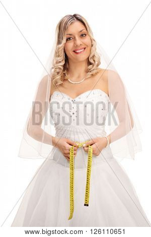 Vertical shot of a blond bride measuring her waist with a yellow measuring tape isolated on white background