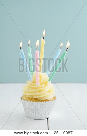 Buttercream birthday party cupcake with multiple burning candles