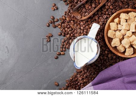 Coffee beans, milk and brown sugar on stone table. Top view with copy space