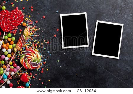 Colorful candies, jelly and marmalade and photo frames on stone background. Top view with copy space