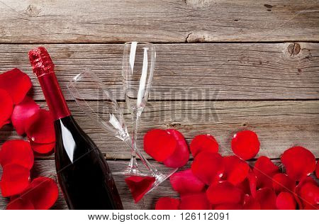 Champagne and rose petals over wooden background