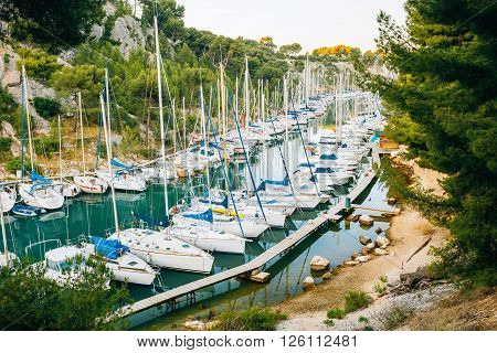 Many White Yachts Boats Moored In Bay. Calanques - A Deep Bay Surrounded By High Cliffs In The Azure Coast Of France
