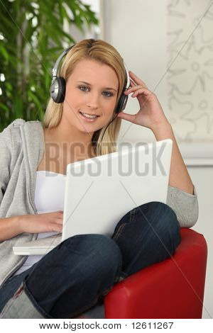 Portrait of a young woman with laptop computer listening to music