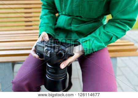 people, photography, technology, leisure and lifestyle - close up of male photographer with digital camera sitting on city street bench