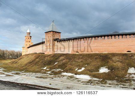 Novgorod Kremlin sunlit under gloomy cloud. Types of towers and walls of Kremlin in Veliky Novgorod.