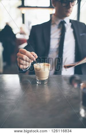 Hand Of Businessman Stirring Coffee In Cafe While Reading Newspaper