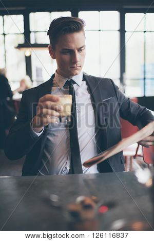 Businessman In Cafe Holding Coffee While Reading Newspaper