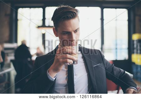 Single Man Drinking Coffee In Cafe While Reading Newspaper