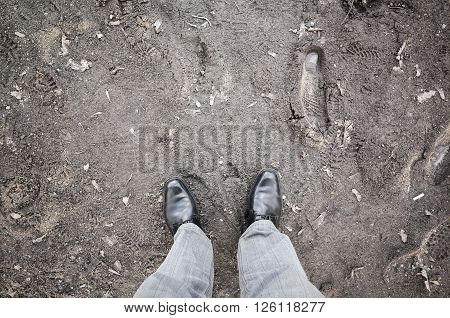 Male Feet In New Shoes Stand On Dirty Rural Road