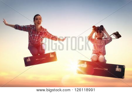 Dreams of travel! Child girl and her mom flying on a suitcase against the backdrop of a sunset.