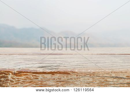 Wooden board empty table in front of blurred background. Perspective grey wood over blur mountain in forest - can be used for display or montage your products. spring season. vintage filtered image.