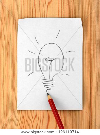 pencil drawing light bulb on paper page on wood background idea concept