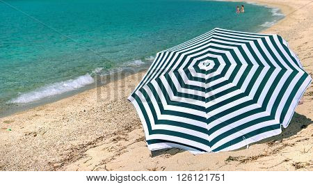 striped sunshade on a beach in Corsica at the turquoise blue sea