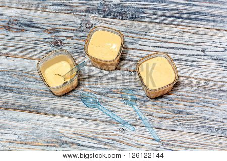 Three jars of yogurt stands on the aged boards