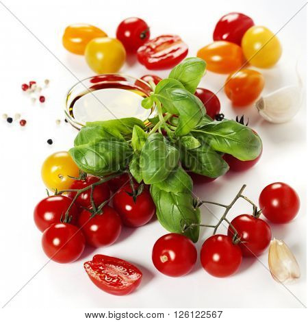 colorful tomatoes and vegetables over white background - Healthy eating, vegetarian or cooking concept
