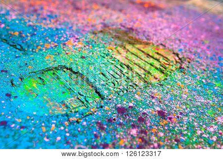 Shoe print on colorful powder background. Closeup