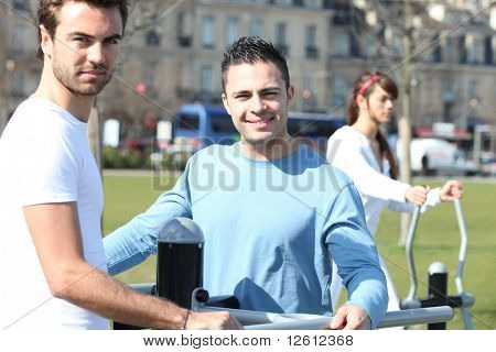Young men and woman doing sports outdoors