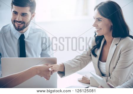 So nice to meet you! Close-up part of young beautiful women shaking hands with smile while sitting at the office table with her coworkers