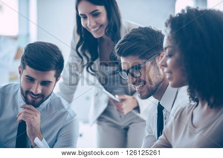 Enjoying working together. Close-up part of group of four people looking down with smile while sitting at office