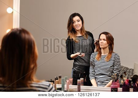 The process of working professional makeup. New service in the beauty salon - make up and be beautiful.Visagist prepares a girl for a date.