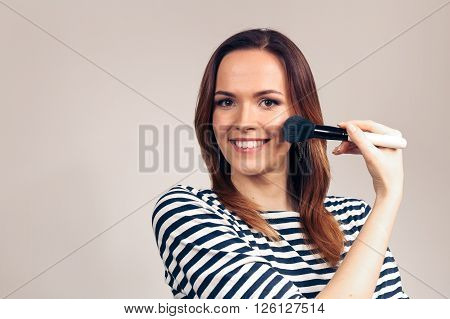 Closeup portrait of woman with makeup brush near face. Beauty woman applying makeup. Beautiful girl looking applying cosmetic with a big brush.