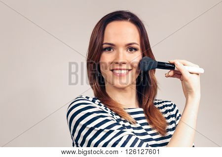 Portrait of a beautiful woman applying makeup in beauty salon. Girl gets blush on the cheekbones and smilling. Powder, rouge.