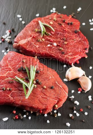 Raw steak with rosemary, salt and pepper on slate plate. Top view