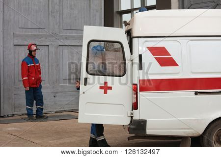 IVANGOROD, LENINGRAD OBLAST, RUSSIA - MARCH 29, 2016: People at the ambulance car during the emergency training at Narvskaya Hydroelectric Power Plant. Built in 1956, it has nameplate capacity 125 MW
