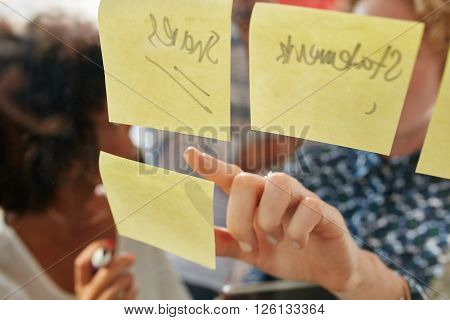 Hand of businesswoman pointing at a sticky note on a glass wall while standing with coworkers in office. Focus on female finger.