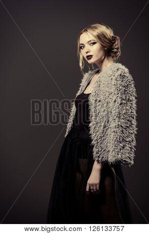 Fashion shot of a beautiful young woman in black evening dress and fur jacket. Studio shot.