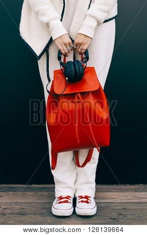 Fashionable beautiful big red backpack and headphones on the arm of the girl in a fashionable white sports suit, posing near the wall on a warm summer night. Warm color.