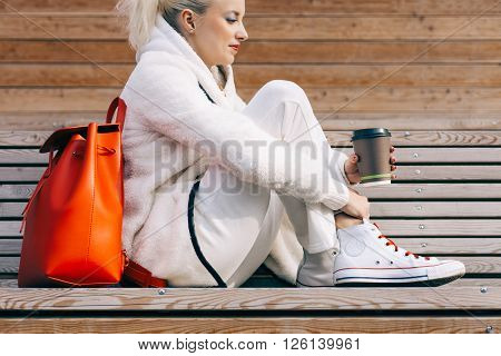 Girl sitting on the bench with a big red super fashionable backpack in the white sports suit and sneakers with cup of coffee on a warm summer evening. Warm colors