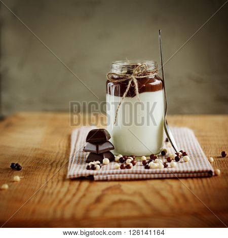 Milky yogurt with chocolate mousse and white, brown chocolate drops on the wooden background.