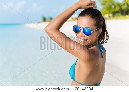 Sexy bikini beach woman having fun dancing in the sun relaxing laughing wearing blue fashion mirror sunglasses. Blissful young girl enjoying summer holiday travel on tropical vacation.