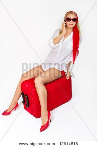 Attractive Woman Sitting On Vacation Suitcase .