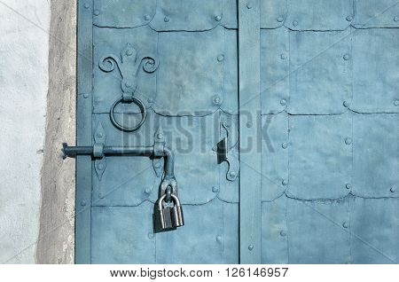 Aged architectural textured background - old iron grey door with plates rivets and old door handle formed as stylized lily.