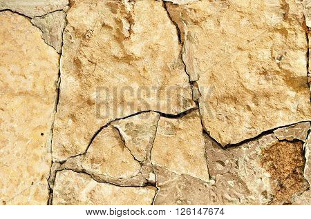Stone background in warm sepia tones - closeup of old rough broken stone with deep cracks