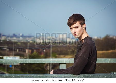 Portrait of sad and gloomy frowning young man standing on the bridge under city road