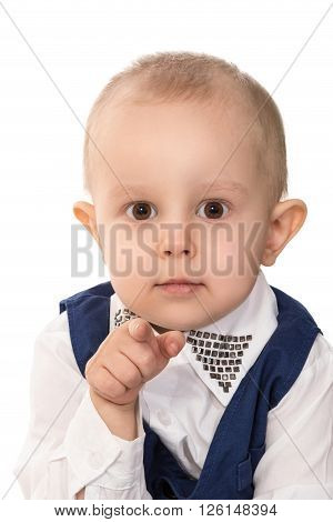 Portrait of a little boy in a blue business suit pointing his index finger at the camera isolated on white background