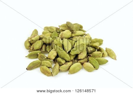 Dried cardamom pile on white background.