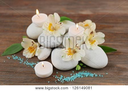 Spa still life with stones, flowers and candlelight on wooden background