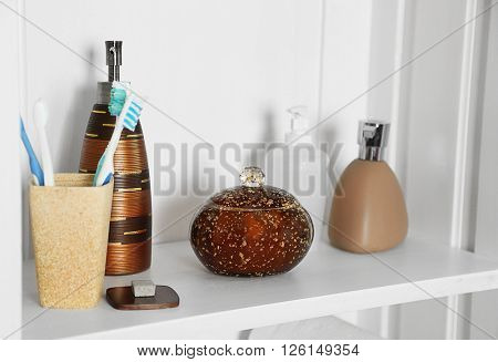 Bathroom set with toothbrushes and dispensers on a shelf in light interior