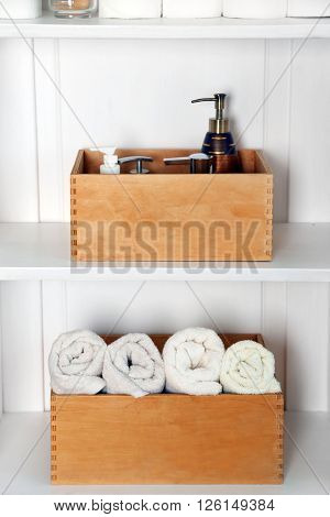 Bathroom set with towels and dispensers in a shelf in light interior