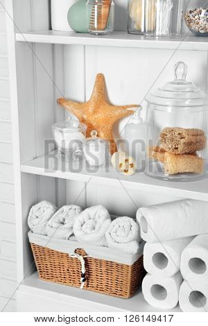 Bathroom set with towels, sponges and starfish on a shelf in light interior