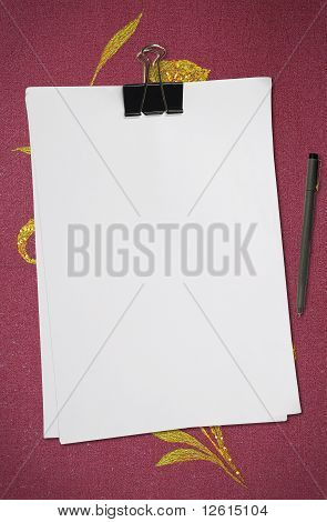 white blank note paper with pen on red fabric