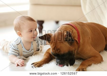 Little baby boy with boxer dog lying at home