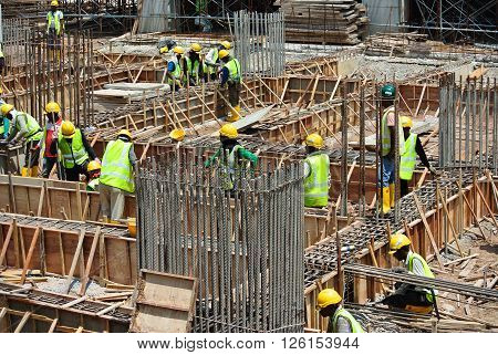 MALACCA, MALAYSIA -MARCH 25, 2016: Construction workers fabricating ground beam reinforcement bar and timber form work at the construction site in Malacca, Malaysia.