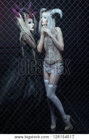 Two women in Gothic dresses are closed in a cage. They carry on the horn head.