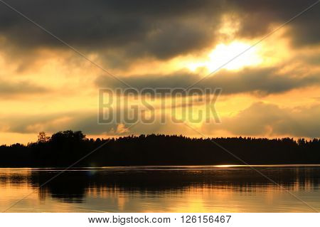 Sunset and calm lake. The sun goes down the horizon and the lake is perfectly calm