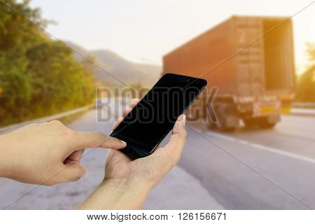 Hand holding and touch screen smart phone,cellphone on roadside with Trucks transporting in background Asian